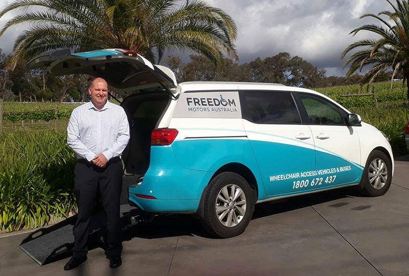 Our friendly Victoria Sales manager Craig Speirs standing in front of a converted freedom access van which allows for people with wheelchairs access and passage to ride along with other passengers, Melbourne Victoria located Freedom Motors Australia business.