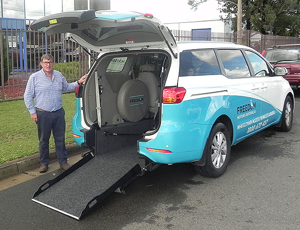 Our friendly Victoria Sales manager Tom Cullen standing in front of a converted freedom access van which allows for people with wheelchairs access and passage to ride along with other passengers, Victoria located Freedom Motors Australia business.